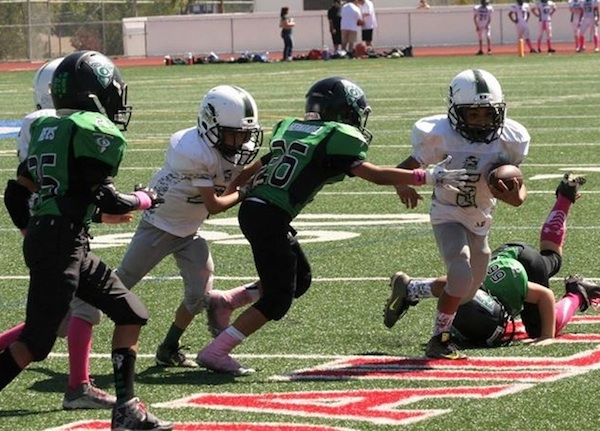 Michael Monty Lopez of the Santa Barbara Sharks Pee Wee team breaks free from a Thousand Oaks tackler during a 44-12 win.