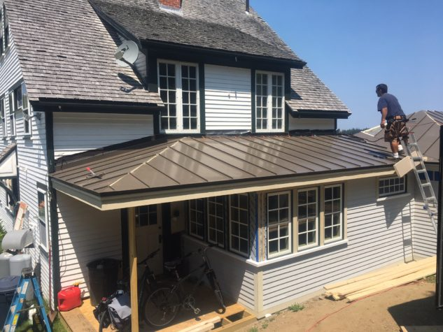 Brown INroof.solar panels are installed on the lower portion of a home with wooden shingles on the upper portion