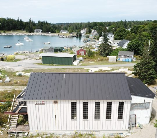 Dark grey INroof.solar panels are installed on a building in the foreground, and several other building and a cove are visible in the background.