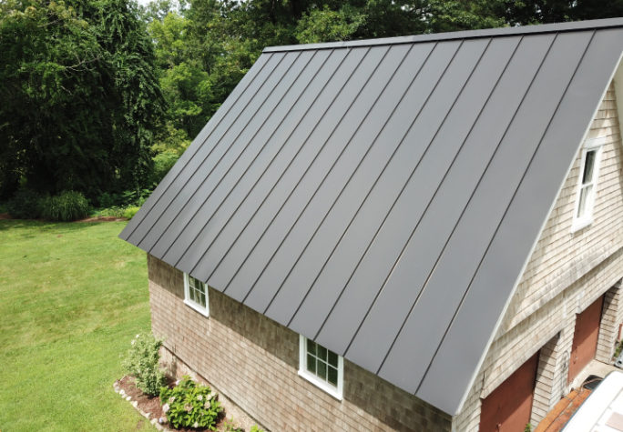 A high side view of a garage with dark grey INroof.solar panels installed.