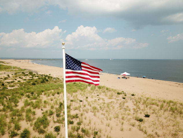 An American flag on a flagpole with the ocean in the background.