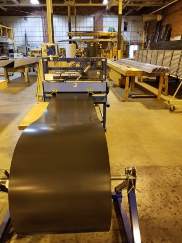 Rolls of dark grey aluminum are being sent through a roll former machine to create the panel shape.