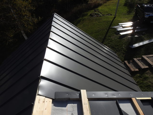 A view of a roof where INroof.solar panels are being installed with uninstalled panels on the ground in the background