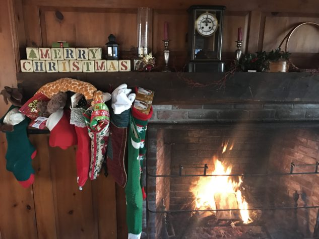 Christmas stocking are hung on a wooden mantel beside a fireplace with a fire going.