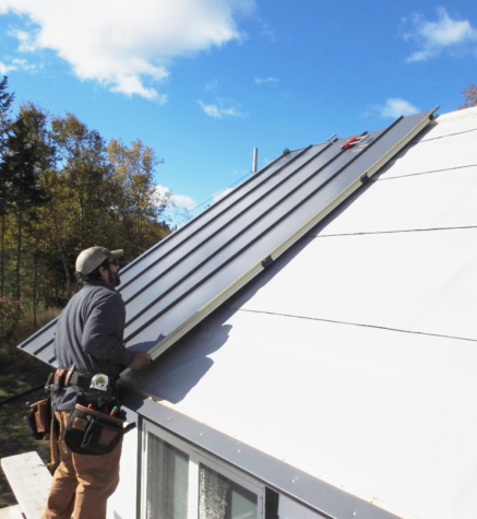 A roofer installs the 5th INroof.solar panel on a small residential roof.