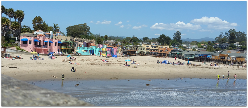 Photo of Capitola Beach as seen from the Capitola Pier on a sunny summer day with colorful beachfront condos lining the shore
