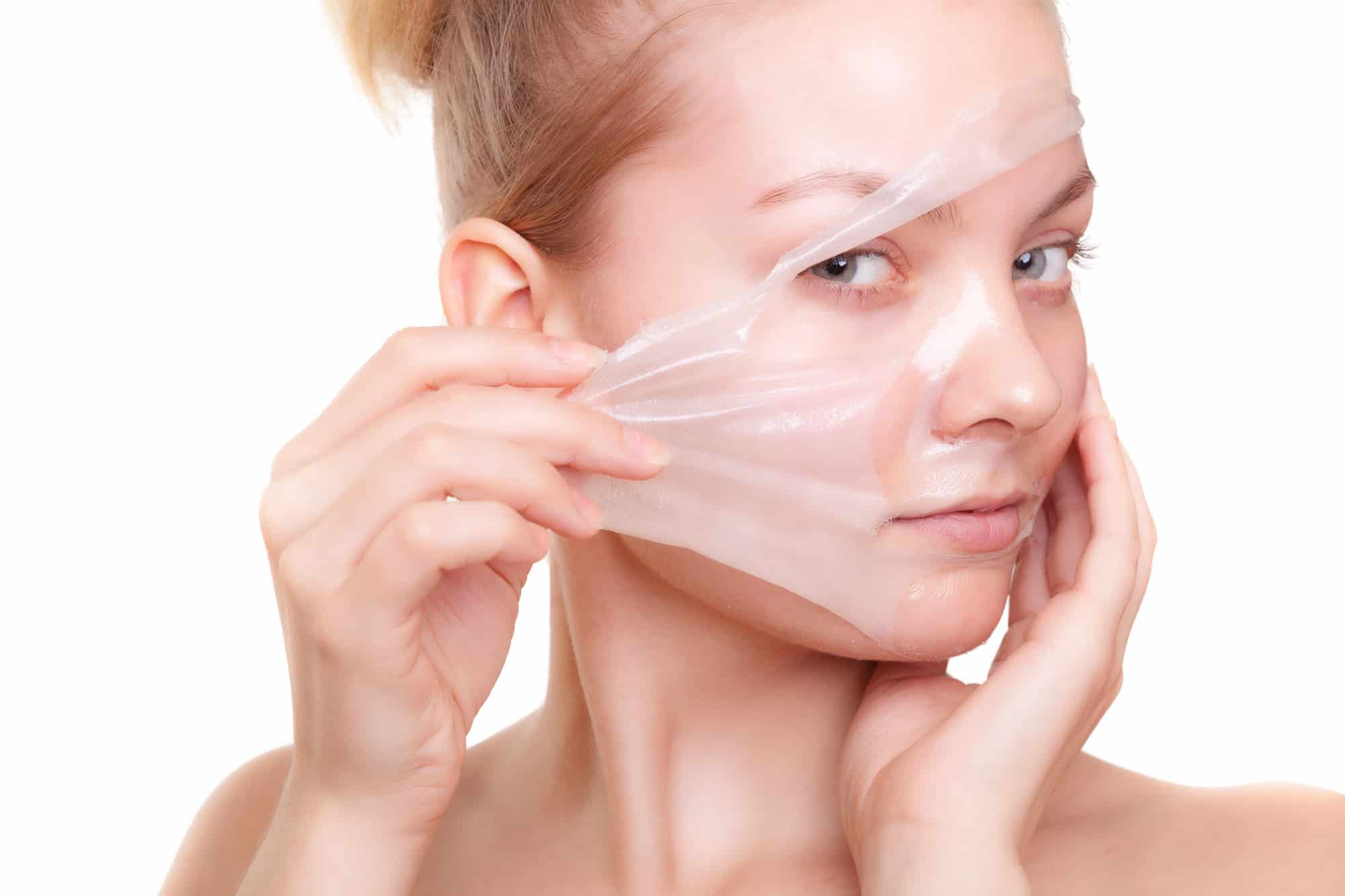 Portrait of girl young woman in facial peel off mask isolated on white. Peeling. Beauty and body skin care. Studio shot.