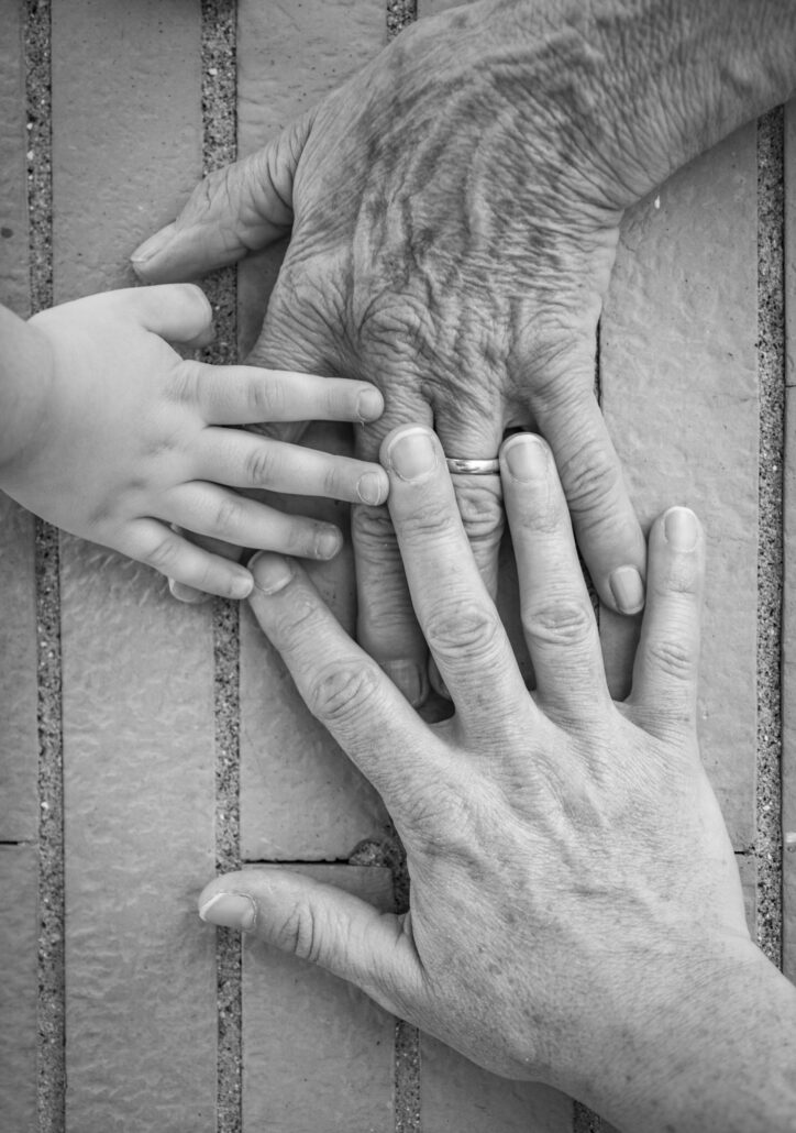 Three hands together, grandmother (elderly woman), mother, daughter, granddaughter. Family unity, love, help, assistance. Age and generational difference. United family.