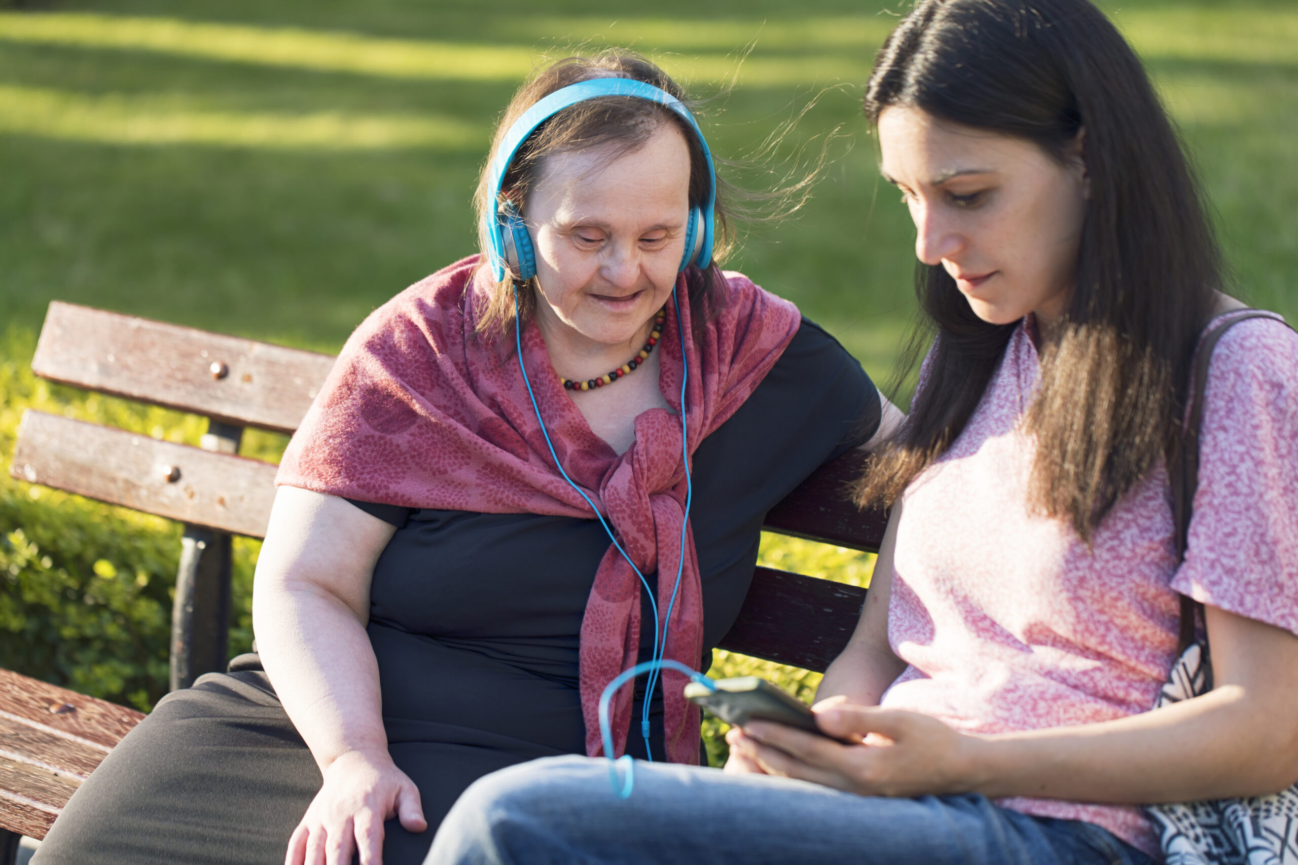 Woman with Down Syndrome and her friend having fun and listening music in a park.