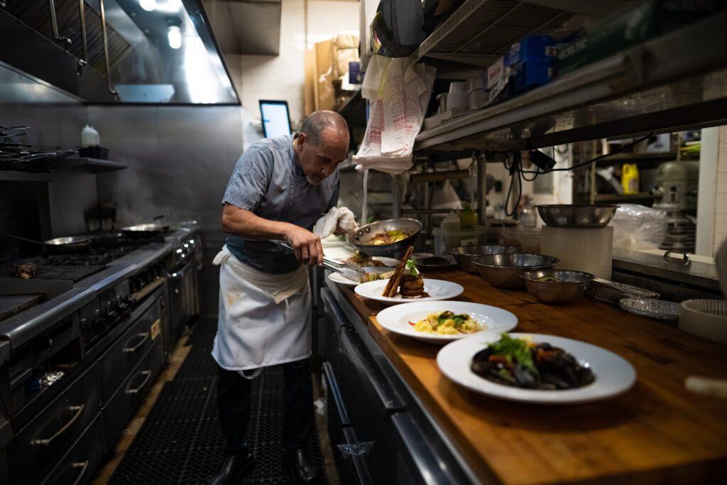 chef plating meals at Espositos Pizza Bar and Restaurant Kitchen