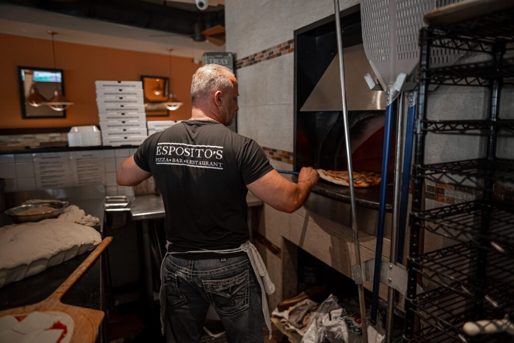 chef putting fresh pizza into the oven at Espositos Pizza Bar and Restaurant
