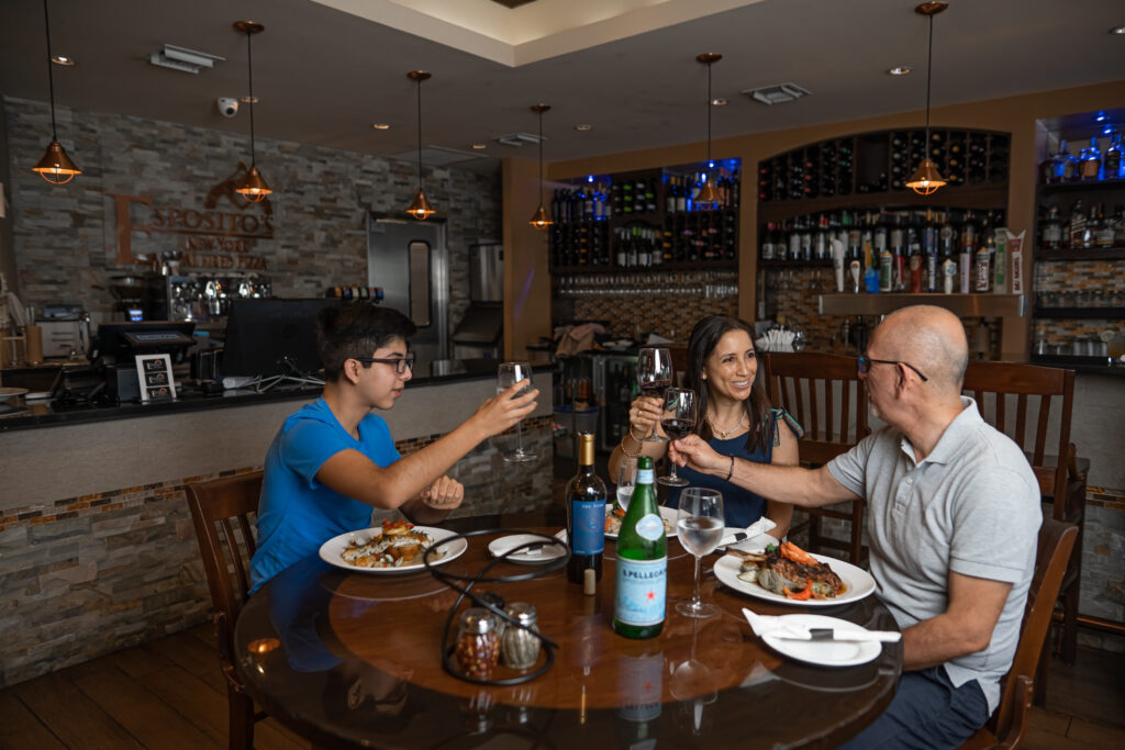 diners toasting drinks at Espositos Pizza Bar and Restaurant