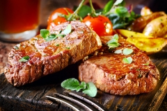 Succulent thick juicy portions of grilled fillet steak served with tomatoes and roast vegetables on an old wooden board
