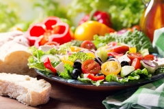 plate of greek salad on wooden table