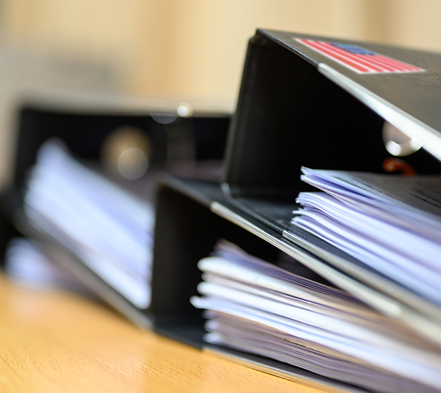 stack of 3 ring binders with documents