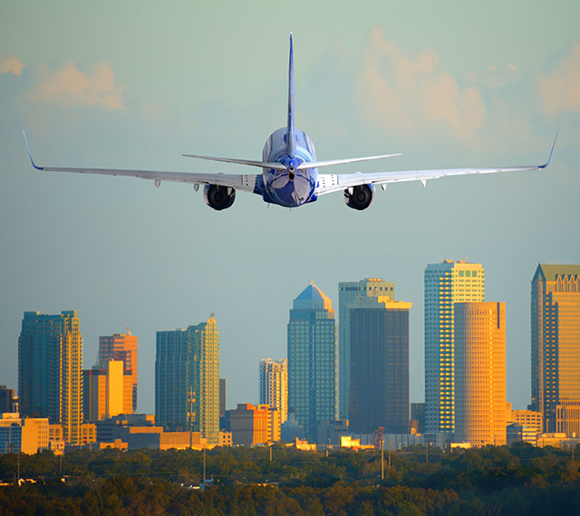 plane landing at Tampa International Airport. Downtown buildings in background
