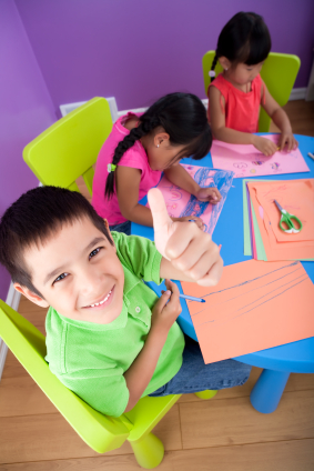 Three Happy Children Coloring On Construction Paper