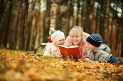 mother reading to children in the fall time