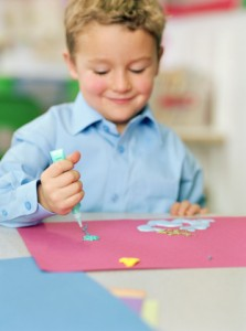 Child pressing a paint glue