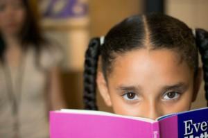 Little girl picking behind a book