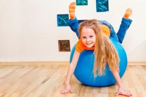 Little girl rolling on a balance ball