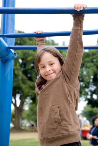 Little girl climbing on monkey bars