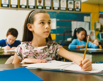 Young Girl Writing in Her Exercise Book in the Classroom