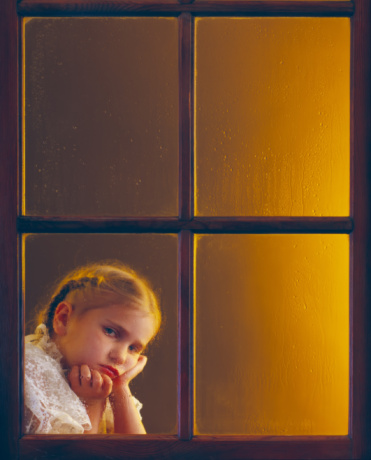 girl looking out the rainy window