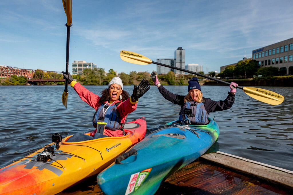 Two women in kayaks on the river.