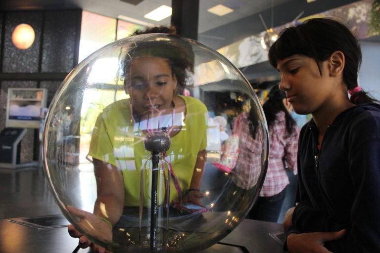 Two young girls at a STEM museum.