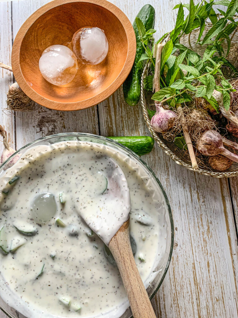 Jajukh on table with ice cubes and basket of garlic and mint