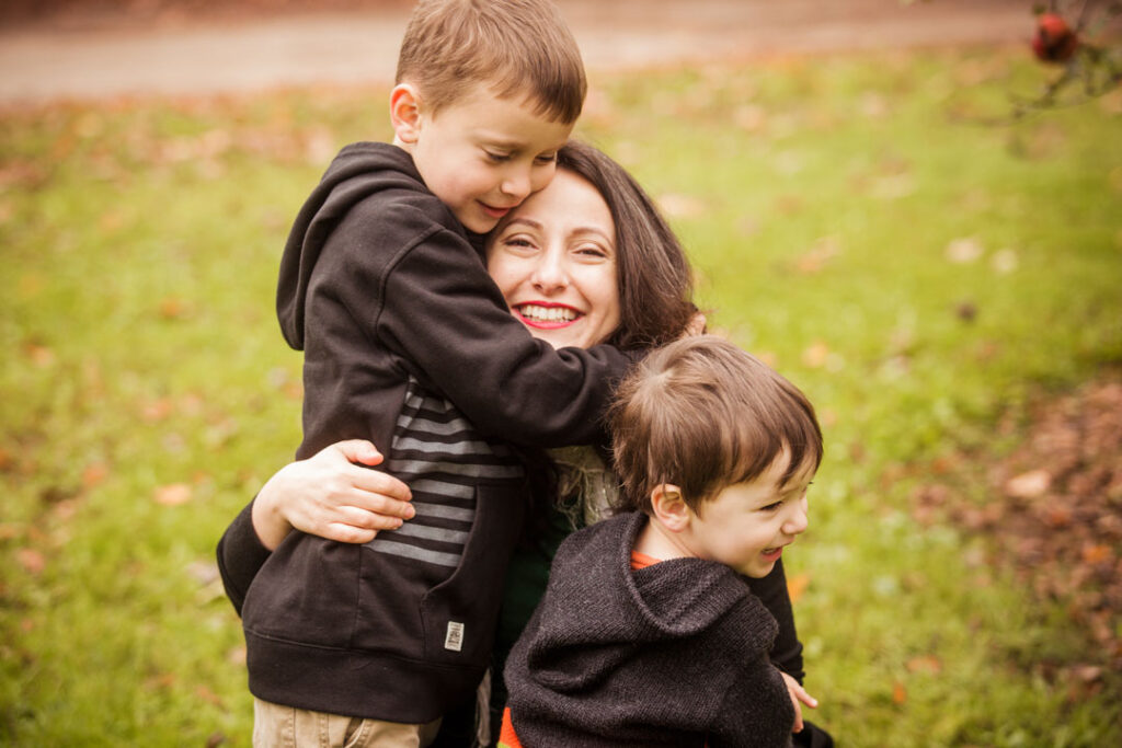 Image of woman hugging two young boys