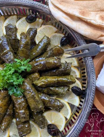 Armenian Sarma on a silver platter garnished with lemon wedges and black olives