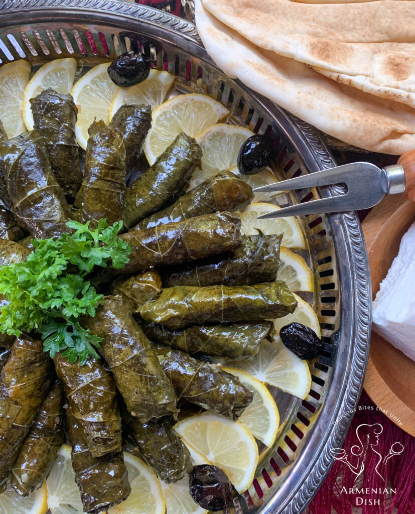 Stuffed grape leaves on table next to pita bread and feta cheese