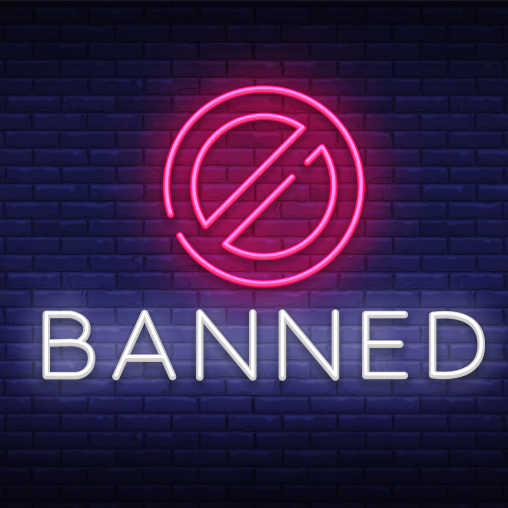 Image saying banned in neon letter against blue background.