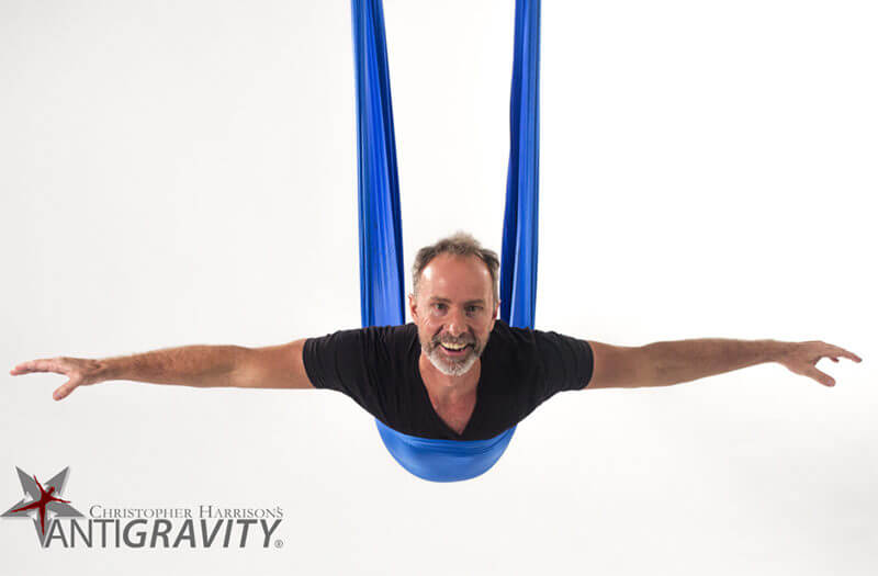Image of Christopher Harrison, founder of AntiGravity® Fitness, facing the camera while lying stomach down in an AntiGravity® hammock with arms outstretched