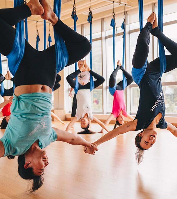 AntiGravity® Group Fitness Class - Women hanging upside down holding hands