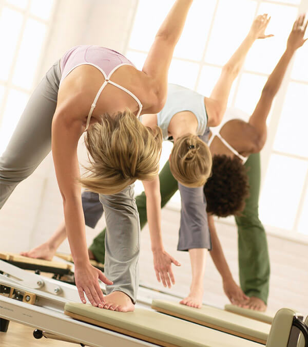 STOTT PILATES® Group Class, group touching toes with one hand, other in the air