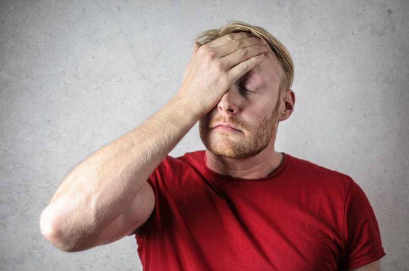 a man in red shirt covering his face