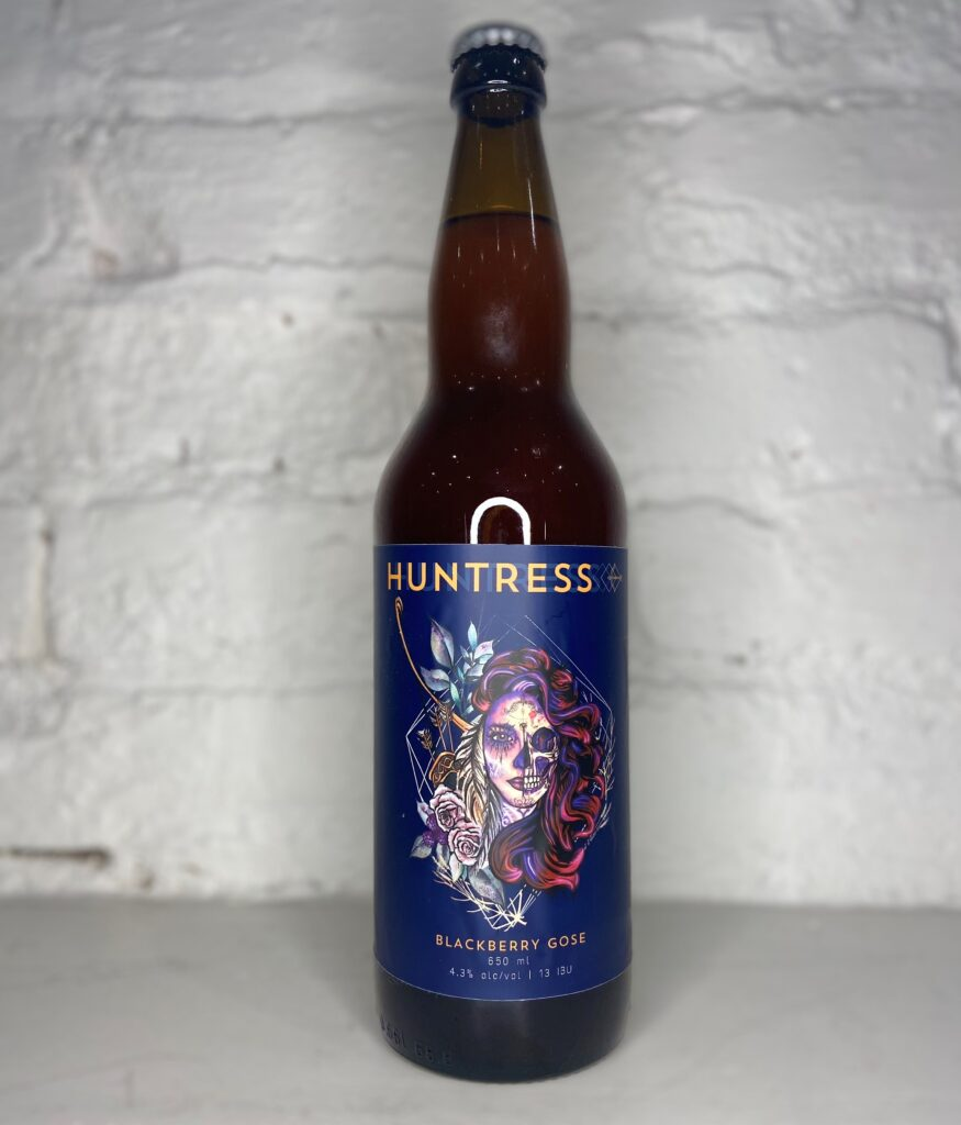 A bottle of 'Huntress,' a beer from Amsterdam Brewing featuring a dark blue label with a woman with half her face made up like a skull and long flowing pink and purple hair.  The style 'Blackberry Gose' is listed below the image.