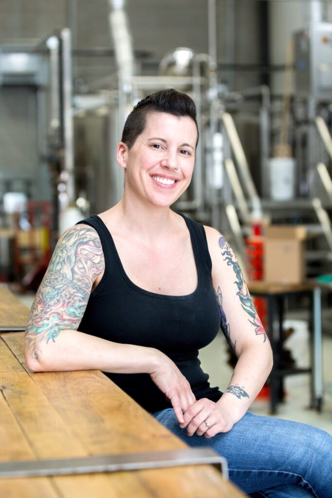 A photo of Erin sitting at the bar at Little Beast's Brewery smiling at the camera.  She has short dark hair, a nose ring and colourful tattoos on both arms and is wearing jeans and a black tank top.