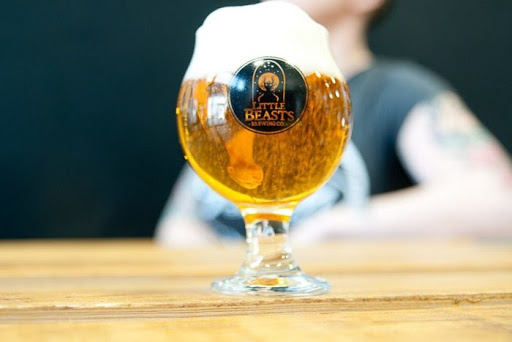 A glass of beer sitting on a wooden bar with the Little Beasts logo on the glass.  Erin is out of focus in the background.