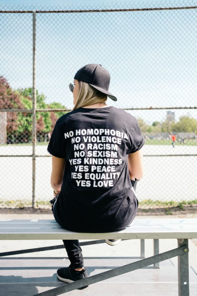 A photo of a person with long blonde hair and sunglasses sitting on a bench outside of a baseball diamond.  The back of their Tshift says  No Homophobia No Violence No Racism No Sexism Yes Kindness Yes Peace Yes Equality Yes Love