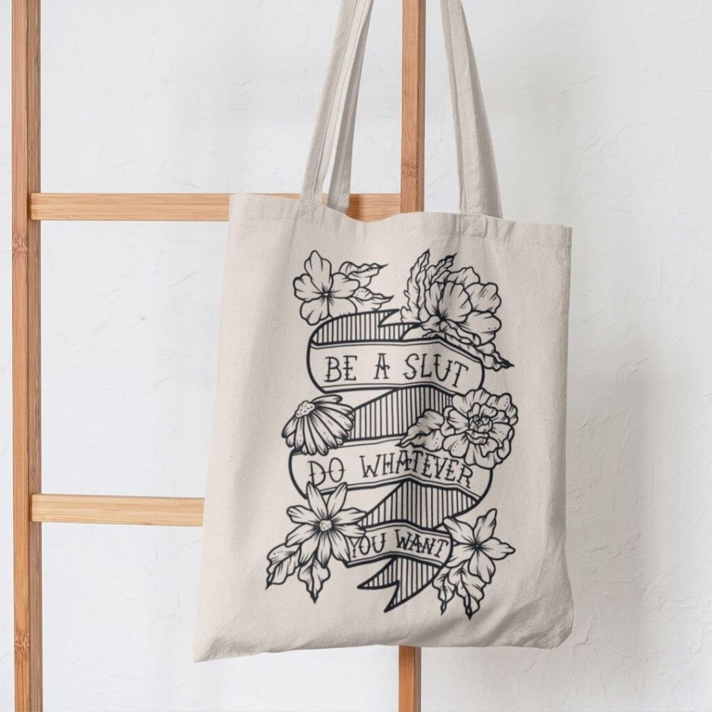A photo of a tote back with Lucky Little Queer's artwork on it.  The tote is beige and the artwork is a black line drawing of a ribbon with lovely flowers around it that says 'Be a Slut, Do Whatever You Want' in all caps.