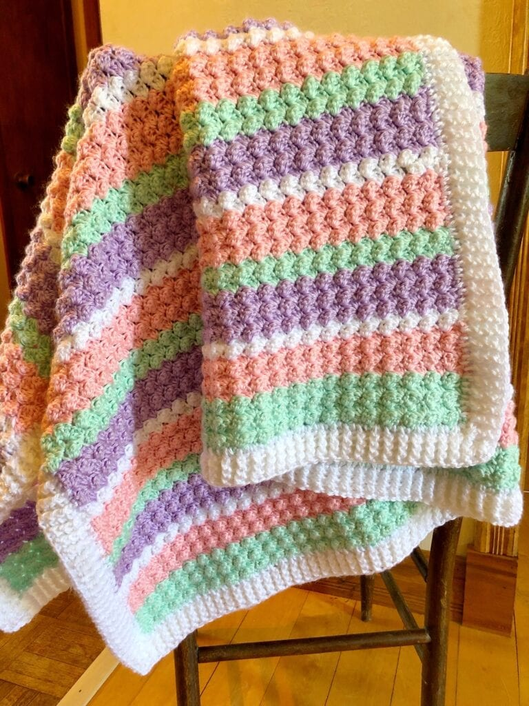 Textured Baby Blanket in Pastel Hanging over the Back of a chair