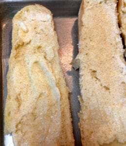 Adding Butter and Garlic Powder to a French Brioche Baguette