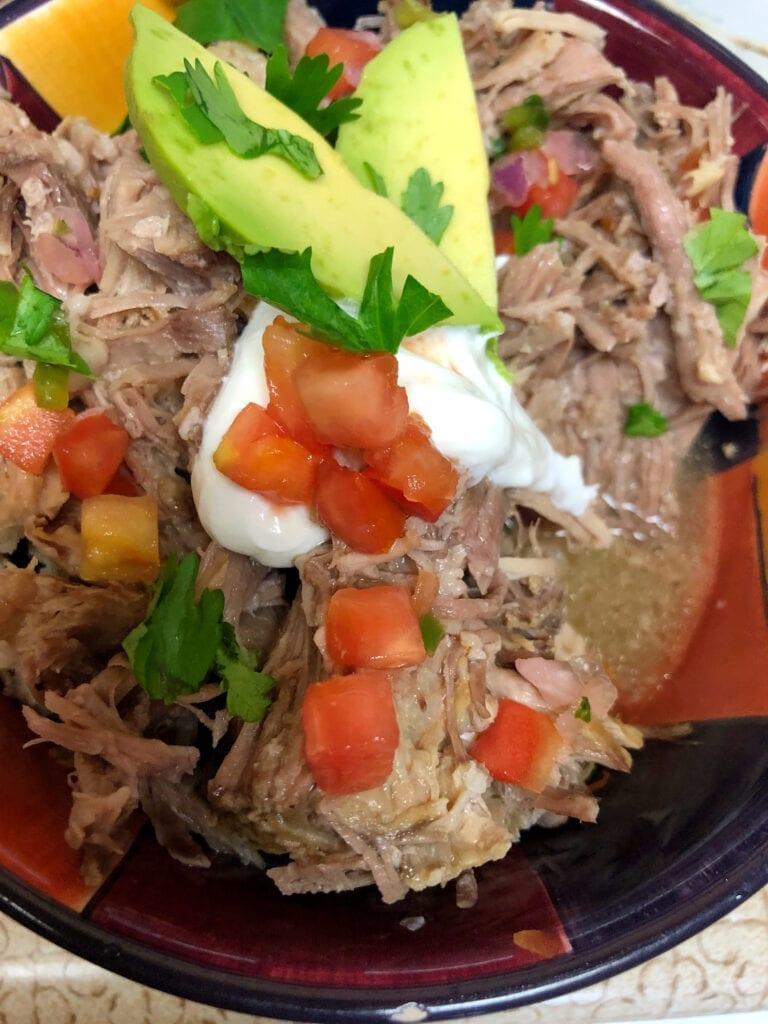 Pork Salsa Verde Served with Avocado Sour Cream Cilantro and Tomatoes