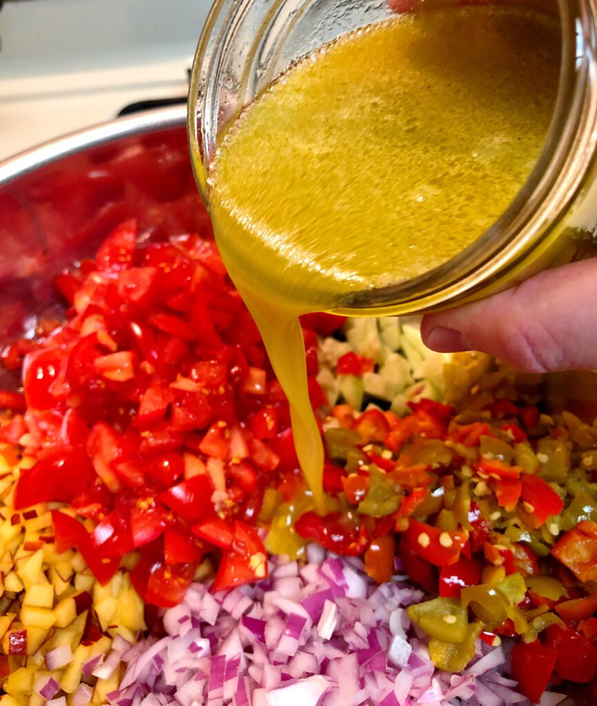 Pouring Salad Dressing Over the Peach Salsa Ingredients