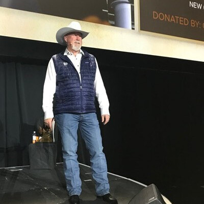 man stands on stage at a fundraising event wearing a cowboy hat