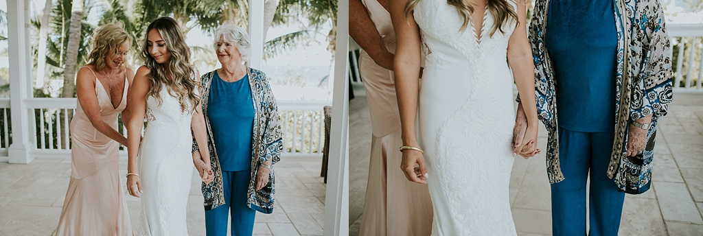 brides mother and grandmother help her with her dress